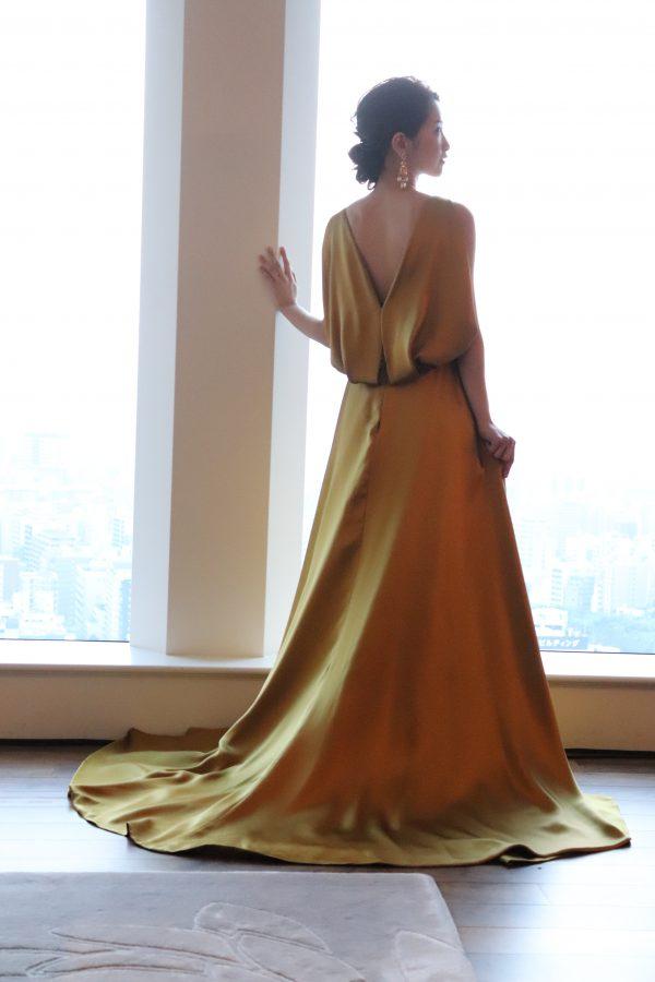 新婦のデコルテから磨かれたボディラインをそのままに、スレンダーラインをイタリアのタロー二社のシルクサテンクレープのダブルフェイス素材に纏い、知的で優美なウエディングシーンを。
